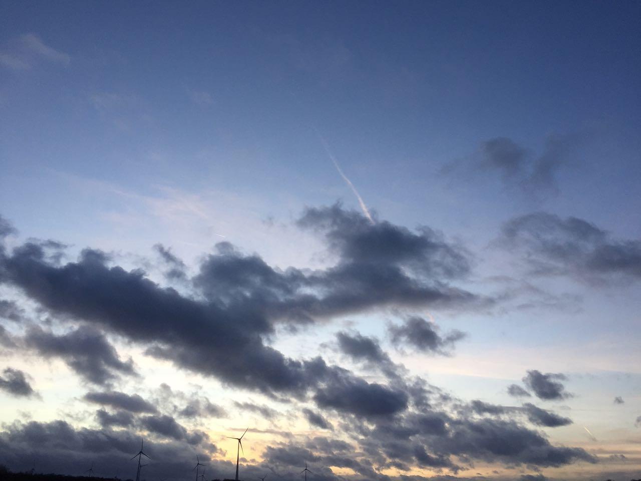 Wolken ziehen über den Himmel und in der Ferne sind Windräder zu sehen. MamaDenkt