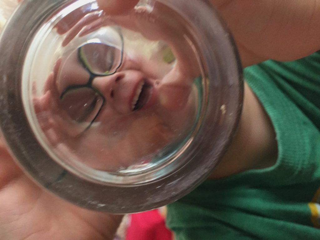 Ein Kind schaut beim Trinken durch den Boden eines Glases und zieht eine Grimasse.